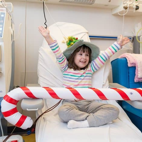 girl in hospital smiling with christmas hat