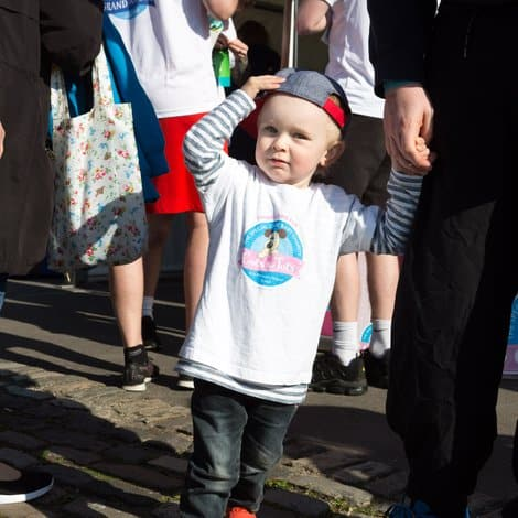 child wearing a cots for tots t-shirt